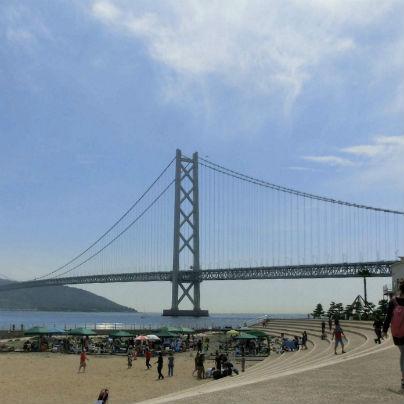画面の中央に明石海峡大橋があり、手前の砂浜では数人の人影があります。
