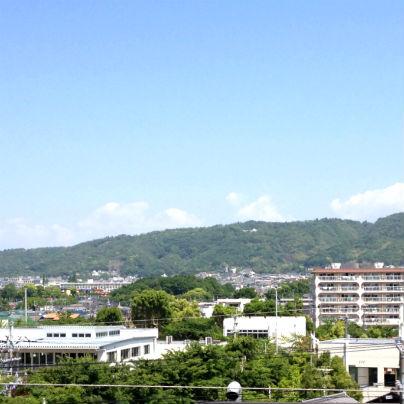 新緑に彩られた山が、手前は箕面の市街。そらは真っ青で山際に白い雲が3つ4つ浮かんでいます。
