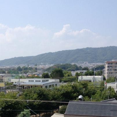市街地の向こうに青くけぶる夏の五月山、空には夏雲が
