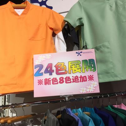 VネックのTシャツにも見えるユニフォームはにオレンジ、右に若草色、その間に24色展開と書いた札がかかっています。