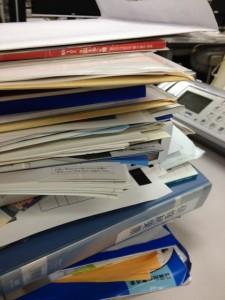 白い机の上にファイルやらカタログやら封筒やらが積み上がっています