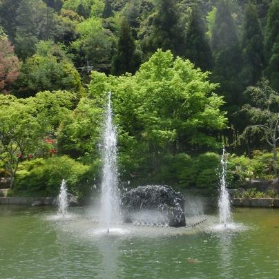 新緑の山を背景に3つの噴水が水を噴き上げています。