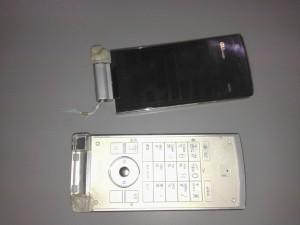 真っ二つに折れた携帯電話はモニター部分とキーボード部分がバラバラになっています