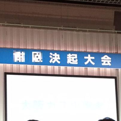 肌色の壁に青色の細長い横幕が貼ってあり、表には○○決起大会と記してあります。その下には大きなスクリーン