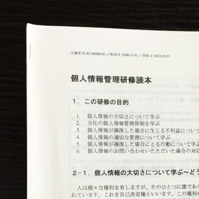 個人情報管理研修読本と題された本が黒い机に載っています。