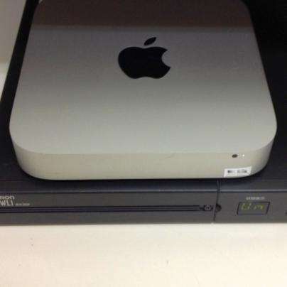 黒い蓄電池の上に銀色で薄く四角い銀色のマックミニが載っています。中央にはリンゴのマークいり。