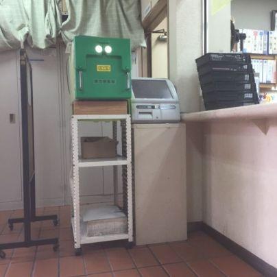 茶色い床のうえに高さ1m近い白い金属フレームの台が置いてあり、その上に緑色の視力検査機が置いてあります。。