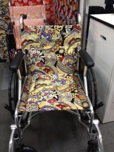 車いすを正面から撮影していて、背もたれシートと座面シートが肌色に牡丹模様の西陣織りになっています