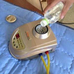 ペットボトルから小さな電気炊飯器のような容器に水をためています。