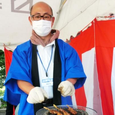 七輪で青いはっぴを着た眼鏡の男が焼き鳥をやいています。