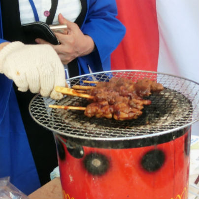 赤い七輪に焼き網を載せて焼き鳥を3本焼いています。
