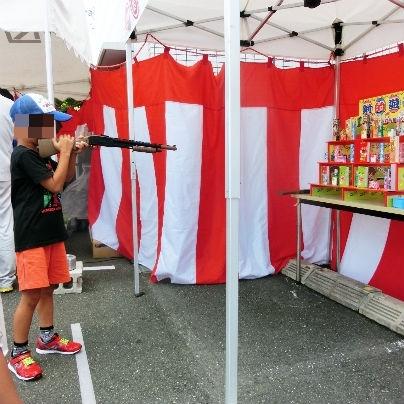 射的ゲームの的に野球帽をかぶった男の子がおもちゃのライフルで撃つところ。