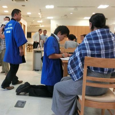 机の前後にお客様。左側に青いはっぴを着た若い男が床に膝建ちになって説明中。