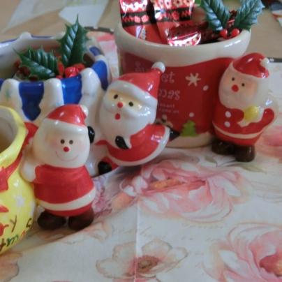 黄色いマグ、青色と白色が縦縞になったマグ、赤いマグ。それぞれ持ち手がサンタクロースです。