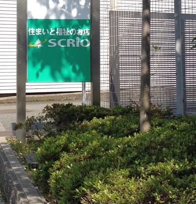 緑色に白い文字で住まいと福祉の店SCRIOと書いてありますが、そこにくっきりと葉の影がウチ利根でいます。