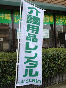店舗前に白地に緑文字で介護用品レンタル・スクリオと書いた幟が1本立っています