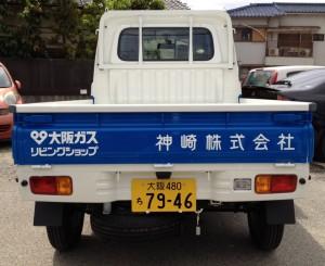 軽トラックの新車を後ろから撮影しています。神崎株式会社のロゴマークは新しいデザインです。