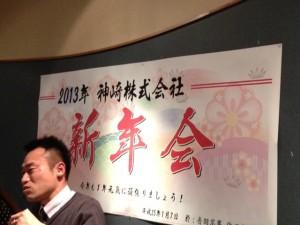 横幅2メートルくらいの白い紙に筆文字で「2013年 神崎株式会社 新年会」と書いてあります。