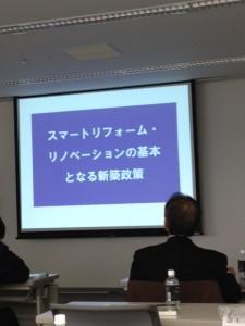 正面のプロジェクタースクリーンに「スマートリフォーム・リノベーションの基本となる新築施策」が写し出されております