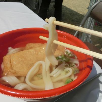 朱色のお鉢にうどん麺と揚げと青ネギ、麺はお箸に引っ掛かっています。