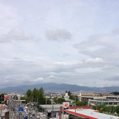手前には出光のガソリンスタンドの赤と白い屋根、その向こうには町並みがひろがり。六甲山の頂きは雲に覆われています