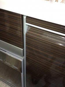システムキッチンでホーロー製ながら木目調の柄の扉が写っています。