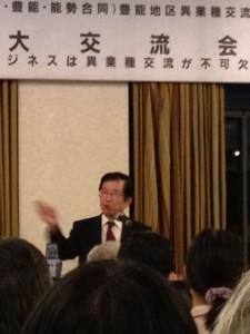シックな背広に白いシャツ、赤系のネクタイをしめた武田教授がマイクの前で講演しています