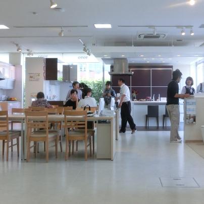 白い床に木製のつくえがひと組。当社のI課長がお客様に説明している様子です。