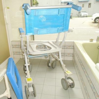 お風呂の洗い場に白いフレームに青い背もたれのシャワーシートが置いてあります。青い座面のシートは外してドア側に立てかけてあります。