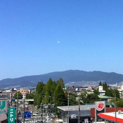 山の手前には町並み、右側には出光のガソリンスタンドで赤と白の看板、左側にはニトリの青緑の看板。そして山の上空は雲ひとつ無い青空で旅客機が飛んでいます。