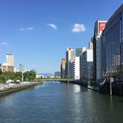 青空には雲が3つばかり、夏の日差し照らされる土佐堀川の両側にはビルが並んでいます。